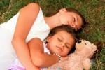 siostry leżące na trawie